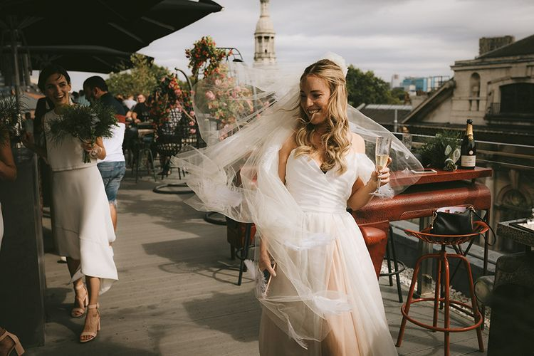 Pre-Ceremony Champagne | Bride in Bespoke Wedding Gown with Blush Underskirt and One Off Shoulder Strap | Fingertip Length Veil Customised with Feathers | Half Up Half Down Bridal Hair | Bike Shed Motorcycle Club Wedding for ELLE Digital Editor | Nigel John Photography