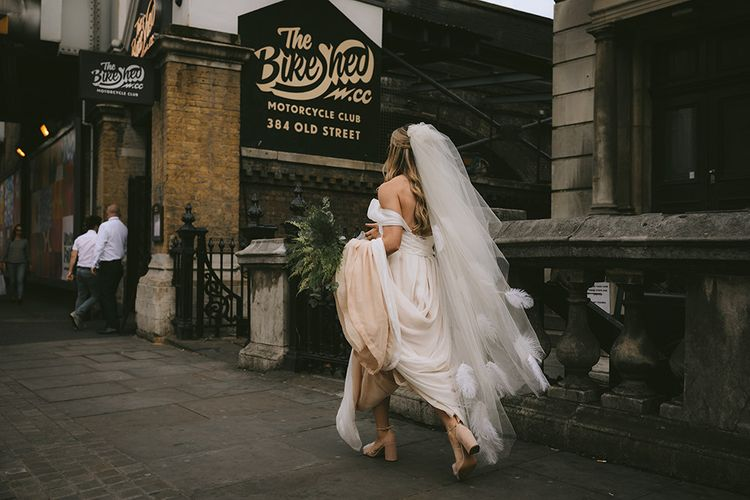 Bride Walking to Wedding Ceremony at The Bike Shed Motorcycle Club in Shoreditch | Bespoke Wedding Gown with Blush Underskirt and One Off Shoulder Strap | Fingertip Length Veil Customised with Feathers | Half Up Half Down Bridal Hair | Nude Topshop Shoes with Pom Pom | Homemade Bouquet of White Flowers, Ferns and Foliage | Bike Shed Motorcycle Club Wedding for ELLE Digital Editor | Nigel John Photography