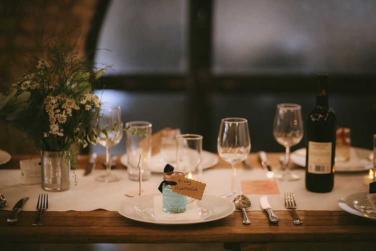 Wedding Reception Décor | Place Setting | Wooden Trestle Tables with White Runner | White Flowers, Ferns and Foliage in Tin Can | Bike Shed Motorcycle Club Wedding for ELLE Digital Editor | Nigel John Photography