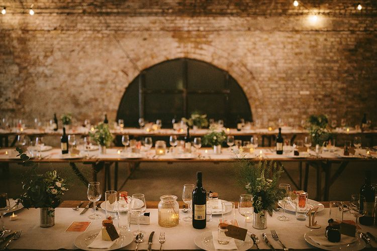 Wedding Reception Décor at The Bike Shed Motorcycle Club in Shoreditch | Wooden Trestle Tables with White Runner | White Flowers, Ferns and Foliage in Tin Can | Tea Lights in Large Textured Jars | Bike Shed Motorcycle Club Wedding for ELLE Digital Editor | Nigel John Photography