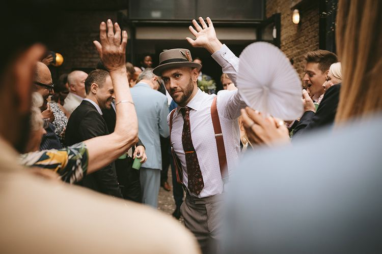 Groom in Grey Puppy Tooth Check Two-Piece Paul Smith Suit with Amber Tie Pin, Pocket Square, Braces and Hat with Feather | Bike Shed Motorcycle Club Wedding for ELLE Digital Editor | Nigel John Photography