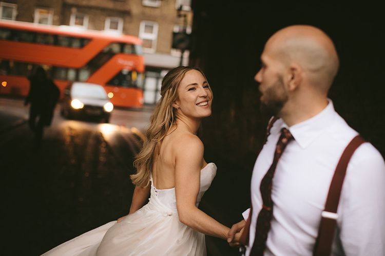 Bride in Bespoke Wedding Gown with Blush Underskirt and One Off Shoulder Strap | Half Up Half Down Bridal Hair | Groom in Grey Puppy Tooth Check Two-Piece Paul Smith Suit with Amber Tie Pin, Pocket Square and Braces | Bike Shed Motorcycle Club Wedding for ELLE Digital Editor | Nigel John Photography