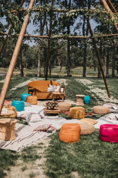Naked Tipi with Foliage and Festoon Lights| Rugs | Footstools | Wicker Tables | Festival Wedding with Naked Tipi Chill Out Area, Lace Bridal Separates, Feather Flower Crown and Protea Bouquet | Serafin Castillo