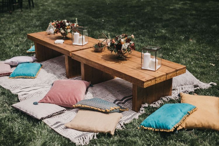 Carpets | Scatter Cushions | Low Wooden Tables | Gold Terraniums | Pillar Candles | Burgundy Flowers | Festival Wedding with Naked Tipi Chill Out Area, Lace Bridal Separates, Feather Flower Crown and Protea Bouquet | Serafin Castillo