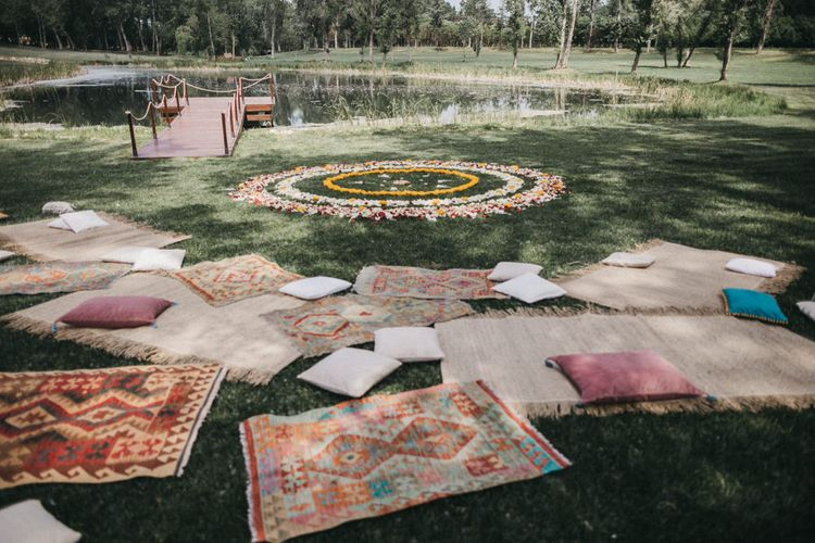 Yellow, Red and White Petal Mandala | Wicker Rugs | Persian Rugs | Scattered Cushions | Festival Wedding with Naked Tipi Chill Out Area, Lace Bridal Separates, Feather Flower Crown and Protea Bouquet | Serafin Castillo
