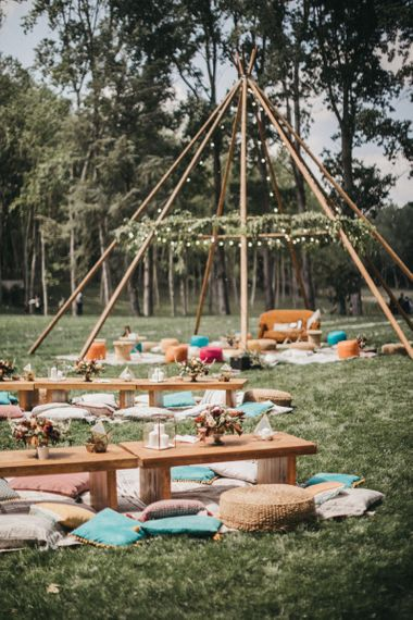 Naked Tipi with Foliage and Festoon Lights| Rugs | Footstools | Scatter Cushions | Low Wooden Tables | Gold Terraniums | Pillar Candles | Burgundy Flowers | Festival Wedding with Naked Tipi Chill Out Area, Lace Bridal Separates, Feather Flower Crown and Protea Bouquet | Serafin Castillo