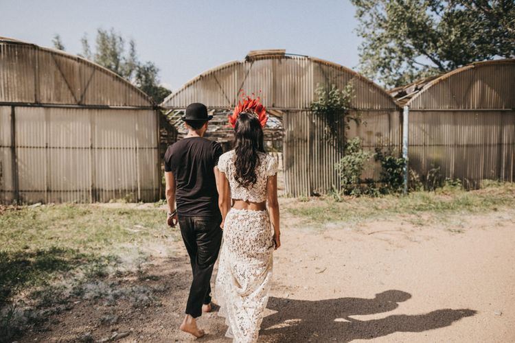 Bride in Lace Separates with Gold Headpiece and Red Feather Crown | Groom in Black T-Shirt and Trousers, Bowler Hat and Sunglasses | Festival Wedding with Naked Tipi Chill Out Area, Lace Bridal Separates, Feather Flower Crown and Protea Bouquet | Serafin Castillo