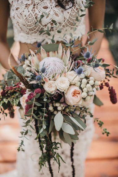Bridal Bouquet with Protea, Peonies, Thistles and Eucalyptus in Burgundy, Blush and White Shades | Bride in Lace Separates with Gold Headpiece and Red Feather Crown | Festival Wedding with Naked Tipi Chill Out Area, Lace Bridal Separates, Feather Flower Crown and Protea Bouquet | Serafin Castillo