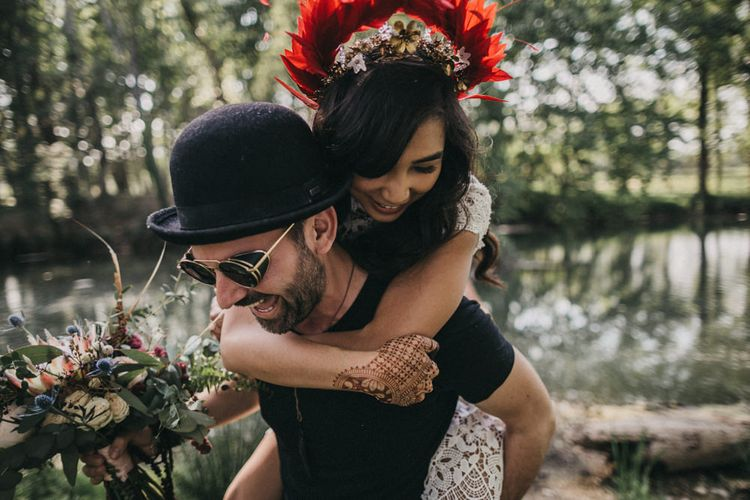 Bride in Lace Separates with Gold Headpiece and Red Feather Crown | Groom in Black T-Shirt and Trousers, Bowler Hat and Sunglasses | Bridal Bouquet with Protea, Peonies, Thistles and Eucalyptus in Burgundy, Blush and White Shades | Festival Wedding with Naked Tipi Chill Out Area, Lace Bridal Separates, Feather Flower Crown and Protea Bouquet | Serafin Castillo
