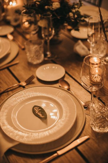 Leaf with Gold Calligraphy Place Setting | Long Wooden Banquet Tables | Charger Plates | Crackle Gold Tea Light Holders | Festival Wedding with Naked Tipi Chill Out Area, Lace Bridal Separates, Feather Flower Crown and Protea Bouquet | Serafin Castillo