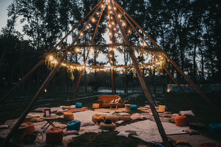 Naked Tipi with Foliage and Festoon Lights | Rugs | Footstools | Scatter Cushions | Mustard Sofa | Festival Wedding with Naked Tipi Chill Out Area, Lace Bridal Separates, Feather Flower Crown and Protea Bouquet | Serafin Castillo
