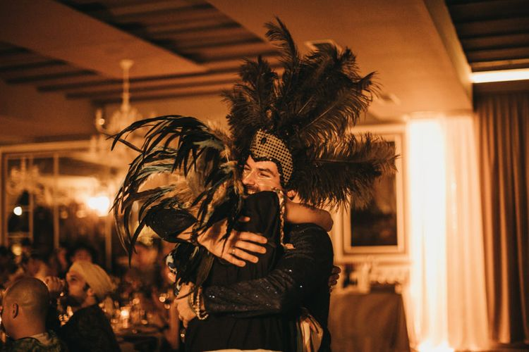Groom in Sparkly Black Shirt with Feather Headdress | Festival Wedding with Naked Tipi Chill Out Area, Lace Bridal Separates, Feather Flower Crown and Protea Bouquet | Serafin Castillo