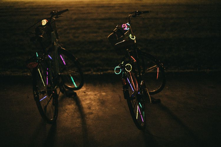 Bikes Decorated with Glow Sticks | Festival Wedding with Naked Tipi Chill Out Area, Lace Bridal Separates, Feather Flower Crown and Protea Bouquet | Serafin Castillo