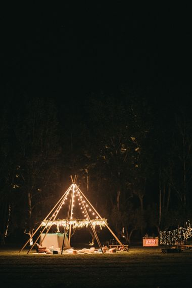 Naked Tipi with Foliage and Festoon Lights | Red Bar Sign Lights | Festival Wedding with Naked Tipi Chill Out Area, Lace Bridal Separates, Feather Flower Crown and Protea Bouquet | Serafin Castillo
