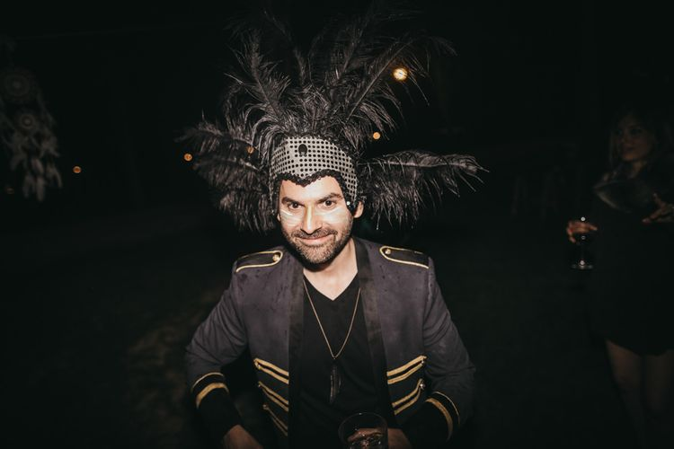 Groom in Feather Headdress, Black and Gold Military Jacket and Feather Necklace | Festival Wedding with Naked Tipi Chill Out Area, Lace Bridal Separates, Feather Flower Crown and Protea Bouquet | Serafin Castillo