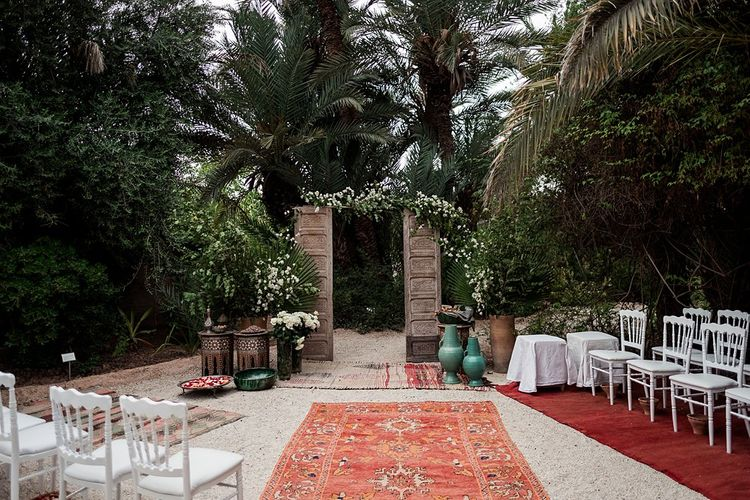 Wooden Door Altar | Moroccan Rugs | Outdoor Ceremony Wedding Decor | Paradise Destination Wedding at Jnane Tamsna in Marrakech, Morocco | Nordica Photography | Matteo Castelluccia Film