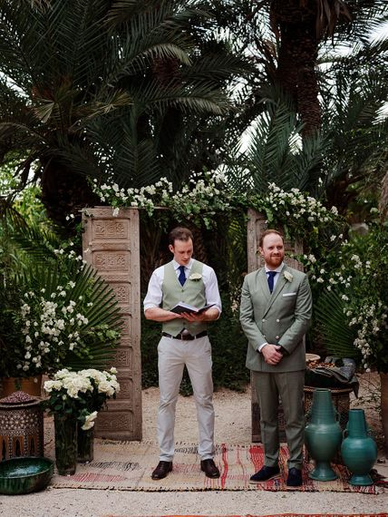Outdoor Wedding Ceremony | Wooden Door Altar Decor | Groom in Green Beggars Run Suit |  Paradise Destination Wedding at Jnane Tamsna in Marrakech, Morocco | Nordica Photography | Matteo Castelluccia Film