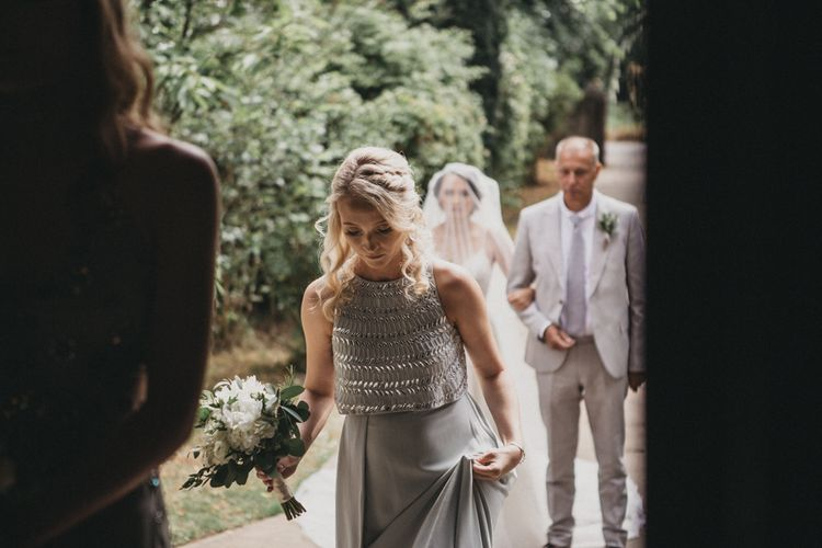 Bridesmaid in Grey Dress with Jewel Detail Walking Into the Church