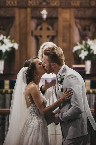 Church Wedding Ceremony with Bride in Martina Liana Wedding Dress and Groom in Light Grey Moss Bros. Suit Kissing