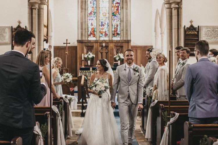 Bride in Martina Liana Wedding Dress and Groom in Light Grey Moss Bros. Suit Just Married
