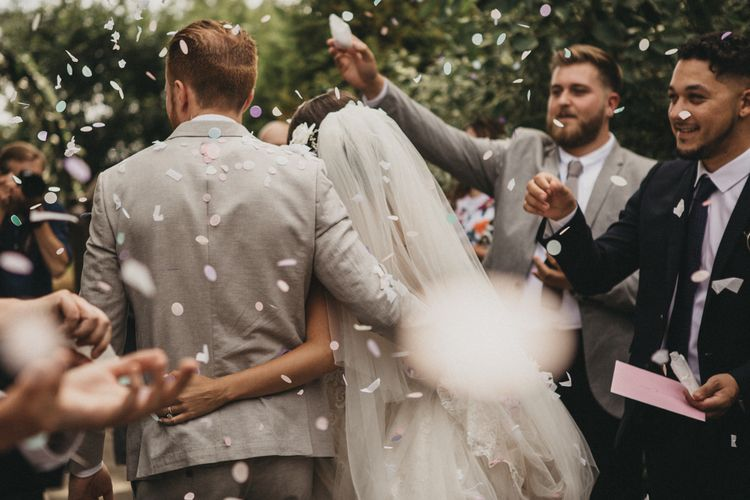 Confetti Moment with  Bride in Martina Liana Wedding Dress and Groom in Light Grey Moss Bros. Suit