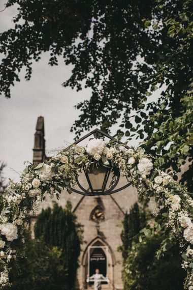 Church Arch Covered in White and Green Wedding Flowers