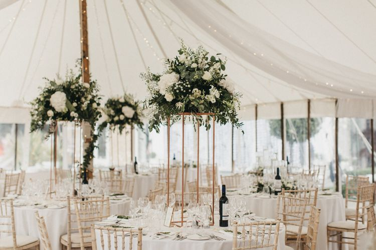 Marquee Wedding Reception Decor with Tall Copper Frame Centrepiece Covered in White and Green Flowers