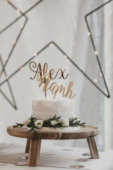 Single Tier Lace Effect Wedding Cake with Personalised Gold Cake Topper on a Wooden Cake Stand