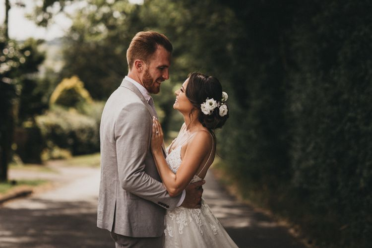 Bride in Lace Martina Liana Wedding Dress and Groom in Light Grey Moss Bros. Wedding Suit