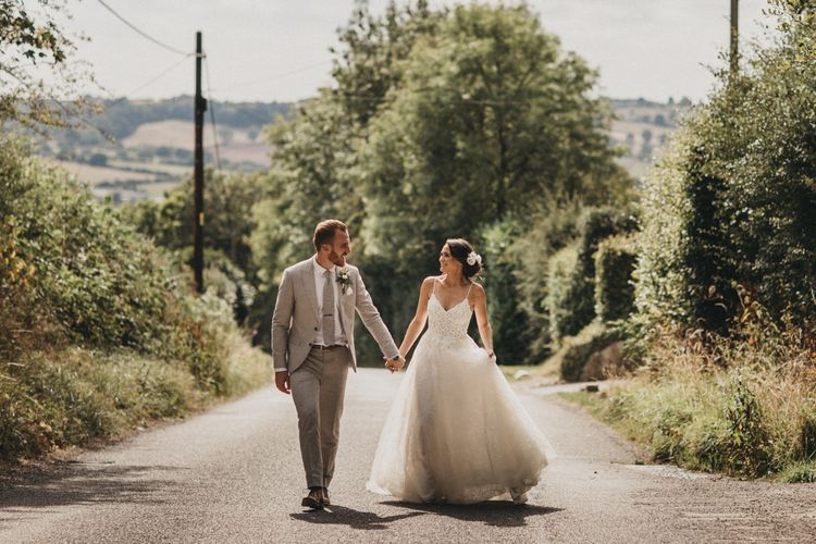 Bride in Lace Martina Liana Wedding Dress and Groom in Light Grey Moss Bros. Wedding Suit Walking Down a Country Lane