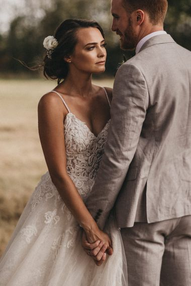 Bride in Lace Martina Liana Wedding Dress and Groom in Light Grey Moss Bros. Wedding Suit Holding Hands