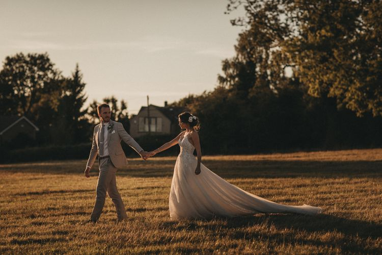 Golden House Portrait of Bride in Lace Martina Liana Wedding Dress and Groom in Light Grey Moss Bros. Wedding Suit Holding Hands