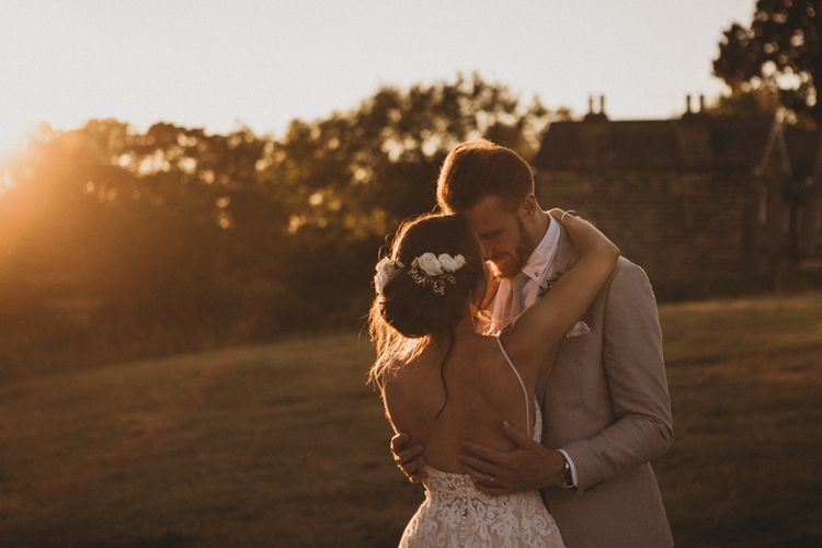 Golden House Portrait of Bride in Lace Martina Liana Wedding Dress and Groom in Light Grey Moss Bros. Wedding Suit Embracing
