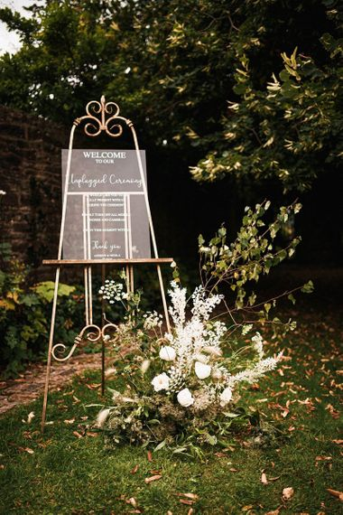 Acrylic unplugged sign with white floral decorations at outdoor Dewsall Court wedding