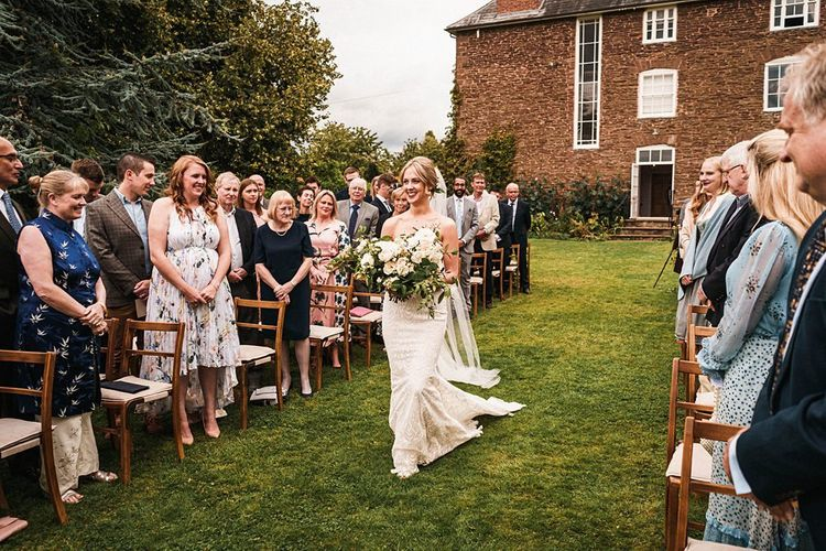Bride walking down the aisle at outdoor Dewsall Court wedding ceremony with white bouquet