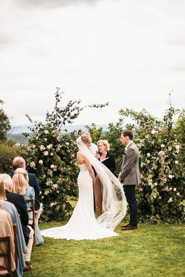 Bride and groom at the alter with white floral arch and long veil