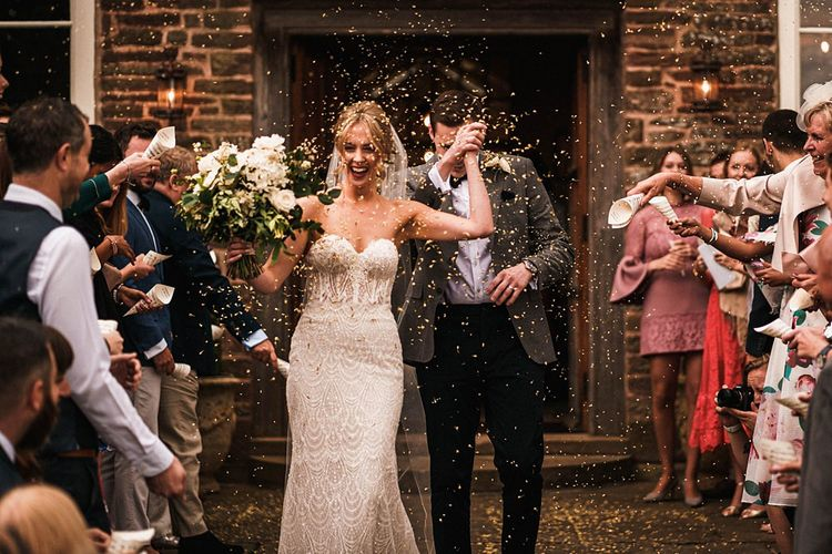 Bride and groom confetti shot at outdoor Dewsall Court wedding ceremony
