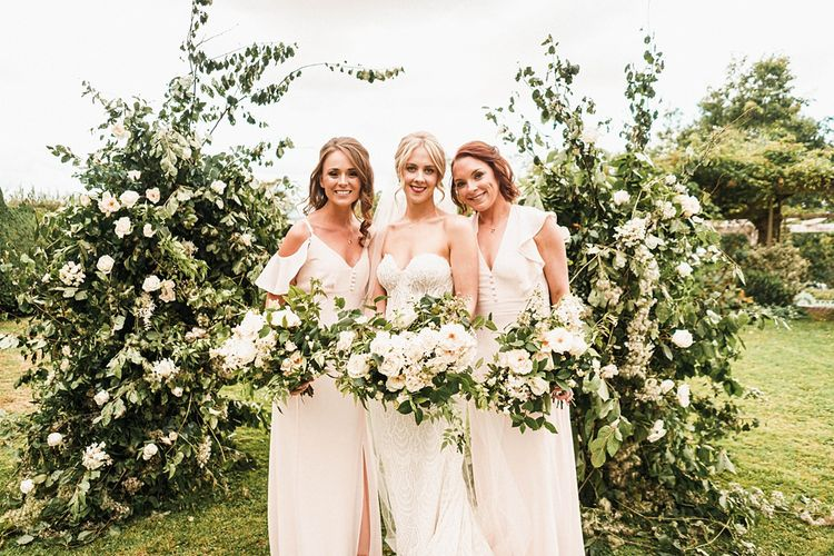 Bride with bridesmaids in cold shoulder dresses and white bouquets with floral arch decor