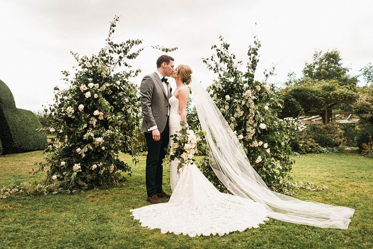 Bride in long strapless dress with groom at outdoor ceremony with floral arch
