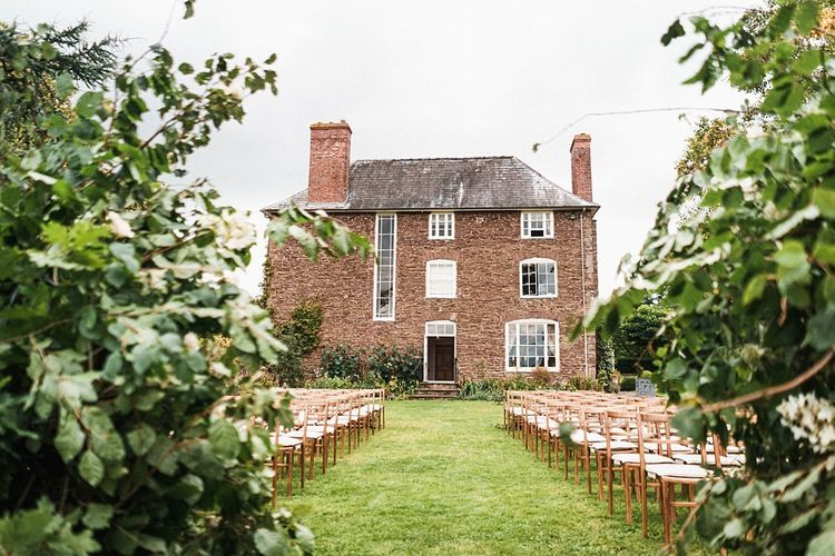 Outdoor autumn ceremony at Dewsall Court wedding with floral arch
