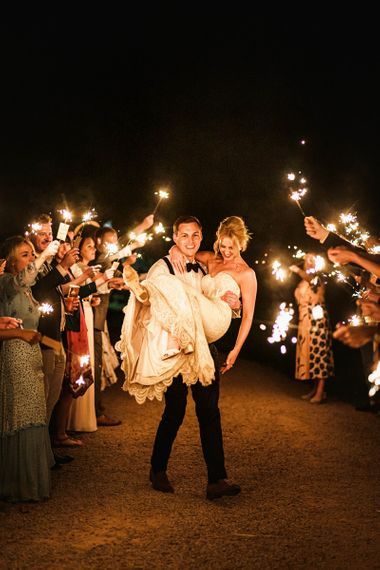 Guests provide a sparkler exit for bride and groom after barn reception
