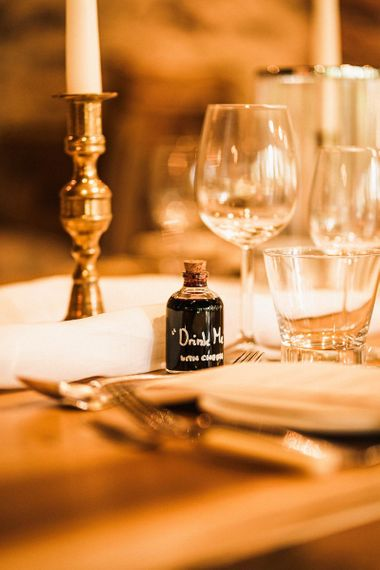 Table setting details with 'drink me' bottle for the speeches at Wainhouse barn reception