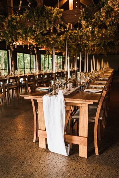 Barn reception venue details with large taper candles and relaxed fabric table runners