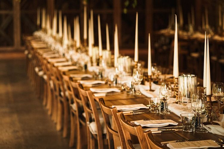 Reception venue details with sophisticated taper candles and relaxed fabric table runners