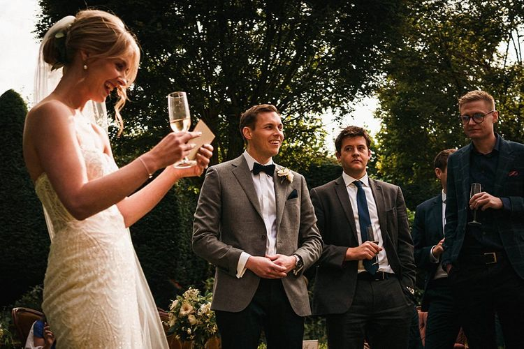 Bride shares a speech in strapless beaded dress with long veil