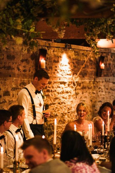 Grooms speech at relaxed barn reception with taper candle decoration