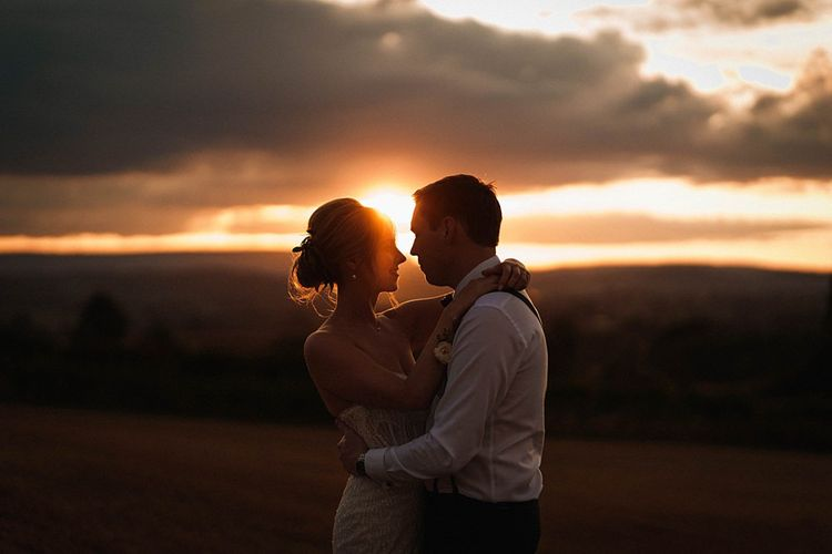 Bride and groom embrace for sunset shot at outdoor autumn day