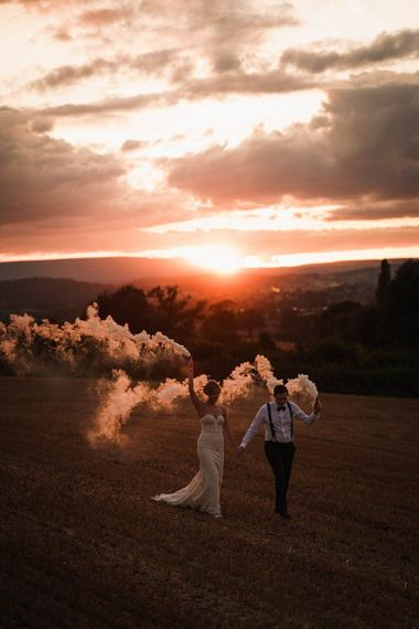 Bride and groom with smoke bombs for sunset shot at outdoor autumn celebration