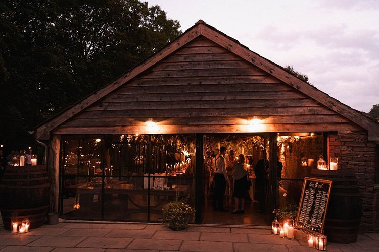Reception details for autumn barn celebration with mirror table plan and candles