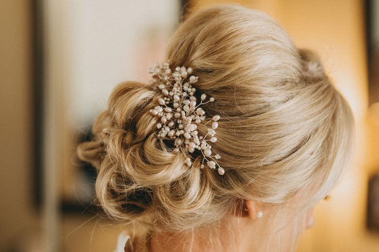 Pinned bridal updo with embellished hairpiece